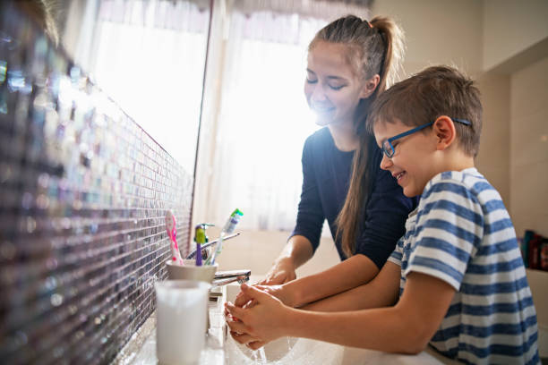 bruder und schwester mit spaß hände zusammen waschen - hände wasser wasserhahn kinder lachen stock-fotos und bilder