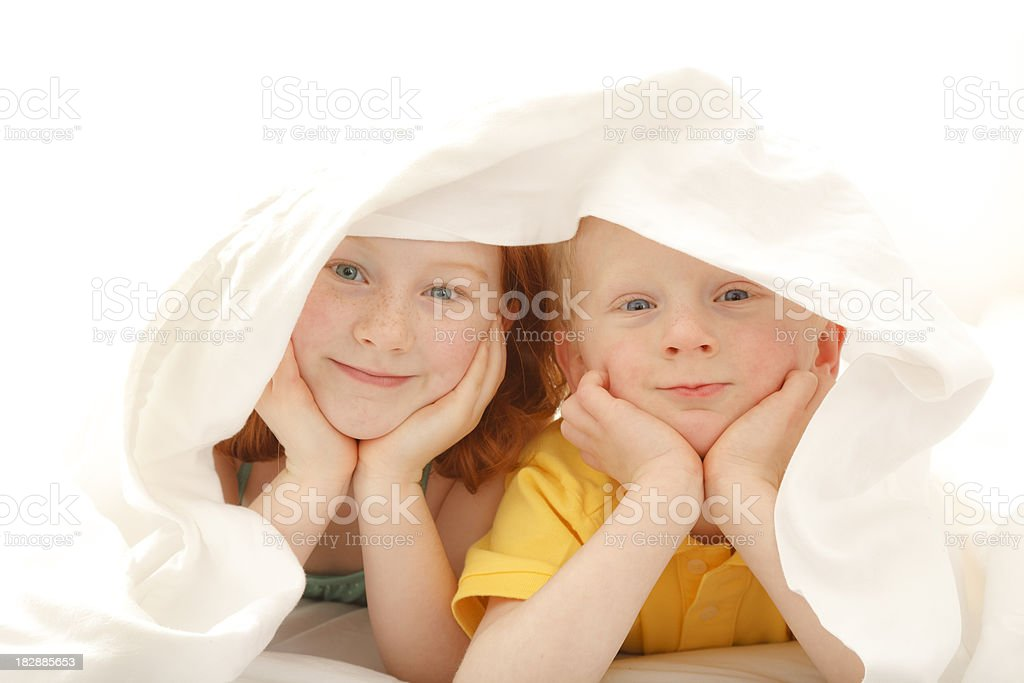 brother and sister hiding under the blankets royalty-free stock photo
