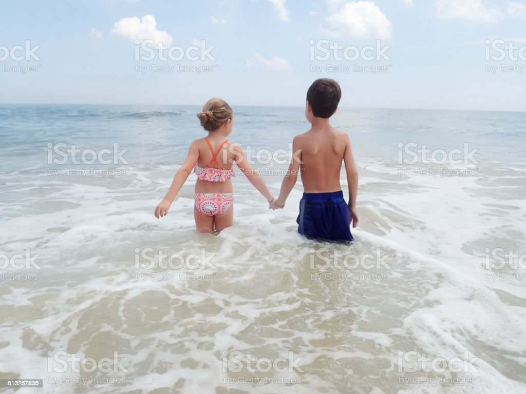 Brother and sister holding hands in ocean stock photo