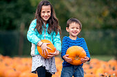 Brother and sister holding pumpkins and smiling in the middle of a pumpkin patch