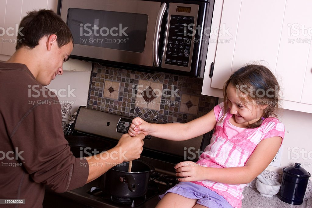 Brother and sister holding spoon together royalty-free stock photo