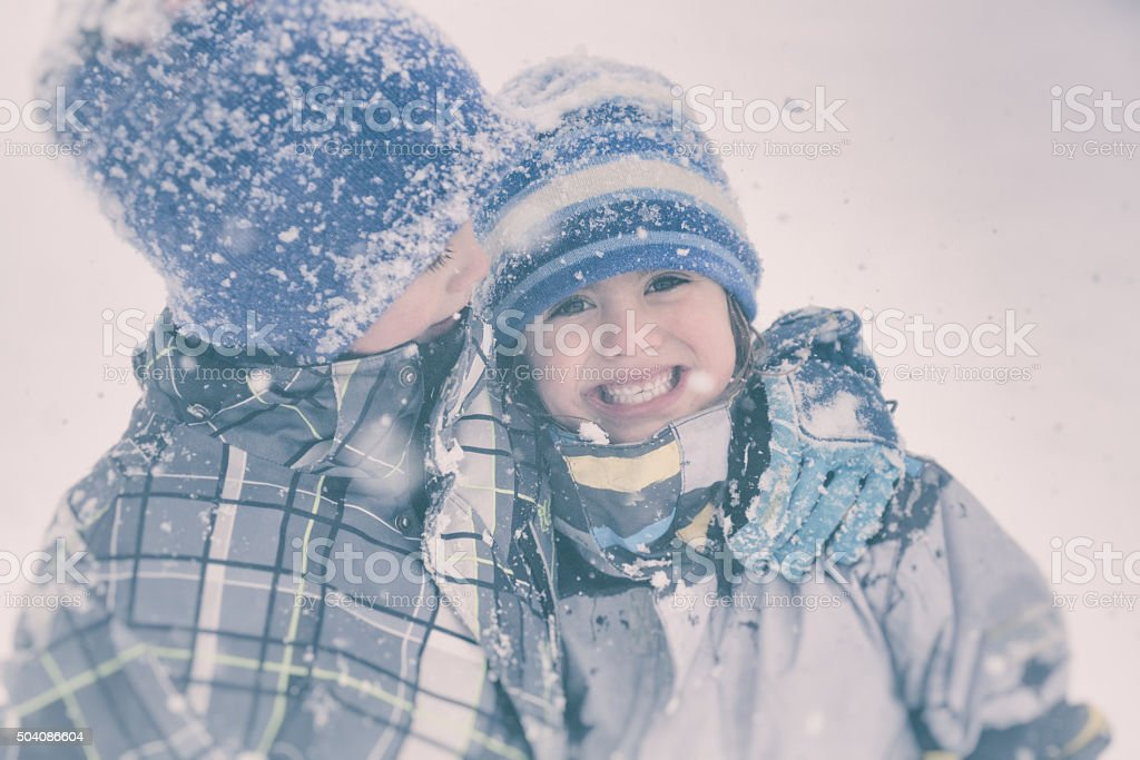 Brother and sister hug in a snowy storm stock photo