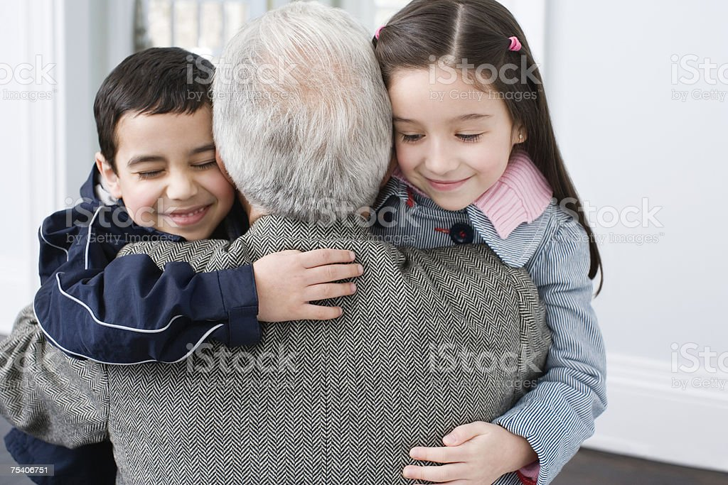 Brother and sister hugging grandfather stock photo