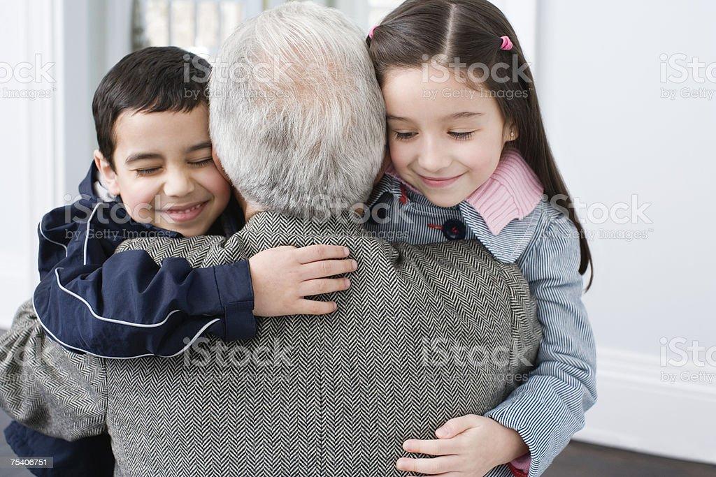 Bruder und Schwester umarmen Großvater – Foto