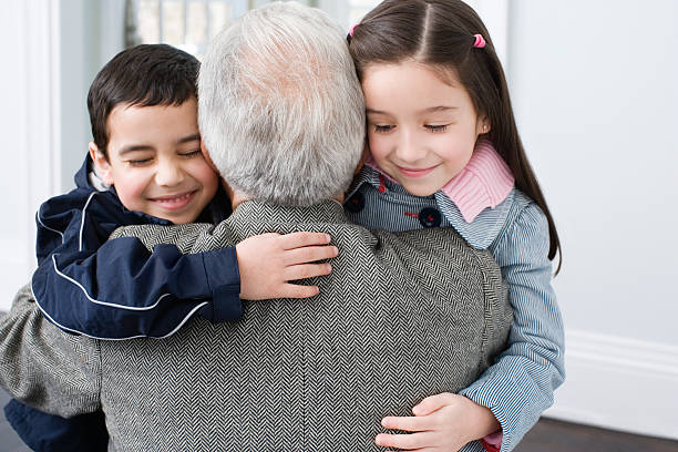 brother and sister hugging grandfather - older brother imagens e fotografias de stock