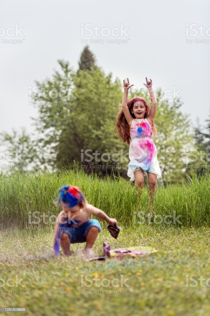 Brother and sister in backyard, playing with colored powder - Royalty-free Bonding Stock Photo