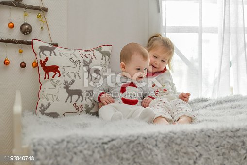 Brother and sister in Christmas pajamas are sitting on the bed with decorations.