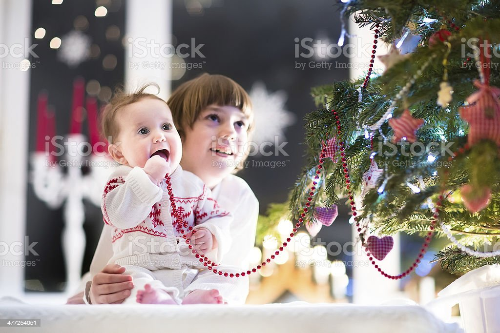 Brother and sister in dark room next to Christmas tree royalty-free stock photo