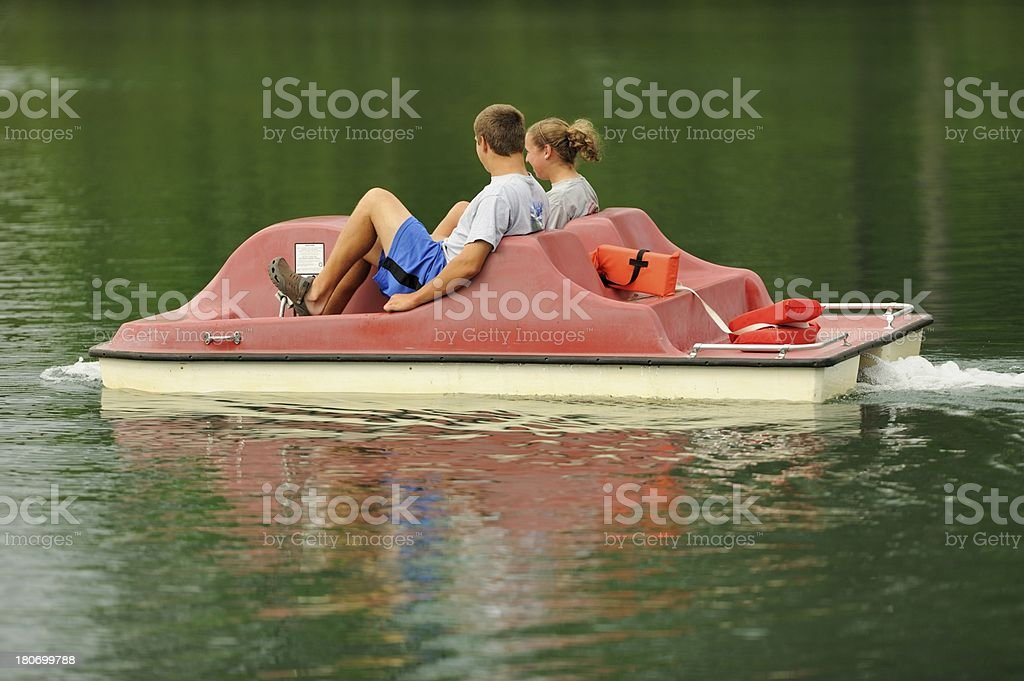 Brother and sister in pedal boat stock photo