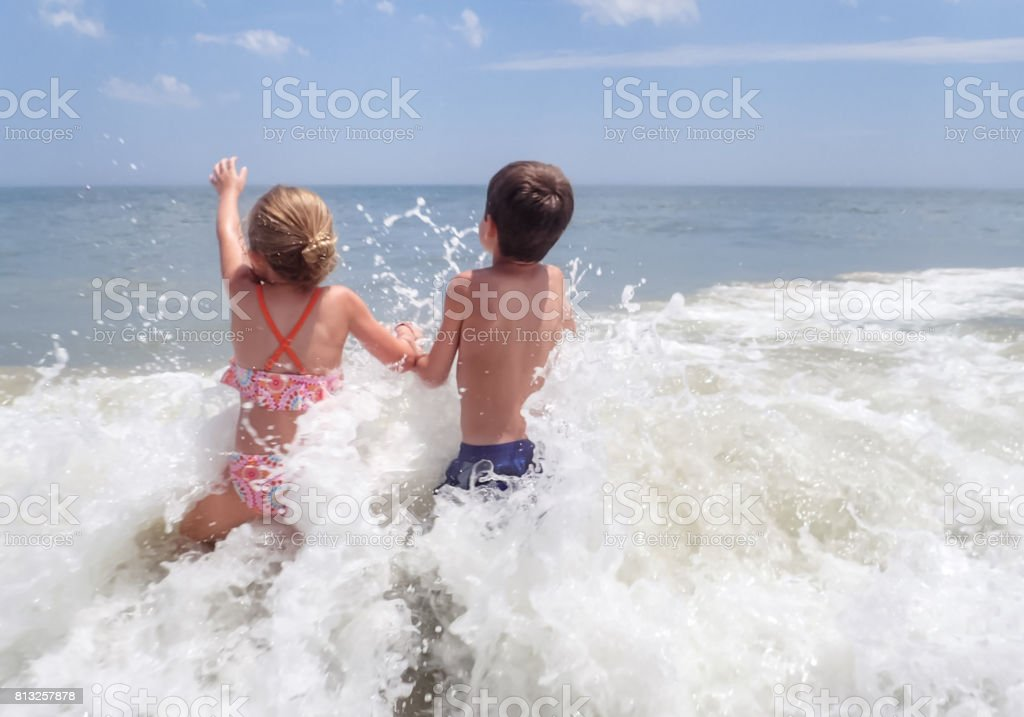 Brother and sister in surf stock photo