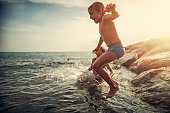 Brother and sister are having fun in sea.  Kida are shouting, laughing and jumping to the sea.\n\n