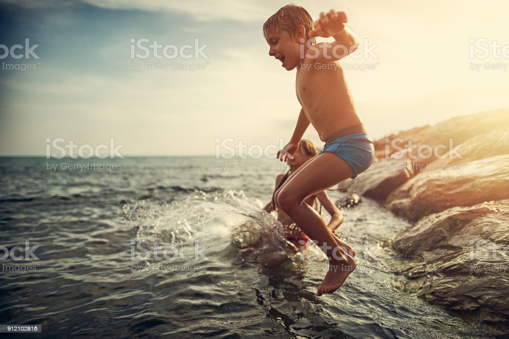 Brother and sister jumping into sea from groyne stock photo