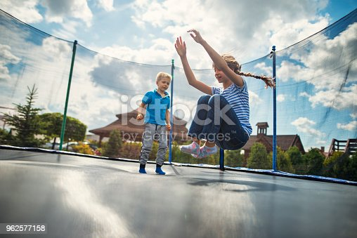 Little boy aged 5 and the girl aged 9 having fun jumping on trampoline. Sunny summer day Nikon D800