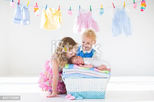 istock Brother and sister kissing newborn baby 542723092