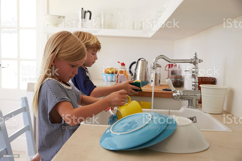 Brother and sister kneeling on chairs to wash up in - foto de acervo