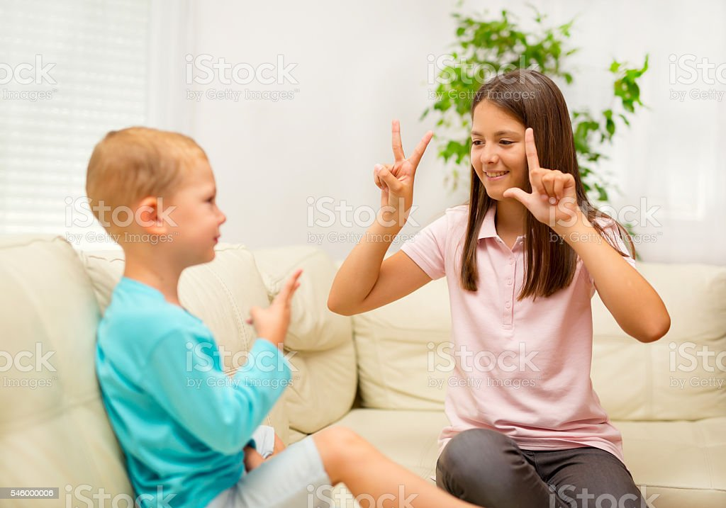 Brother and sister learn sign language at home stok fotoğrafı