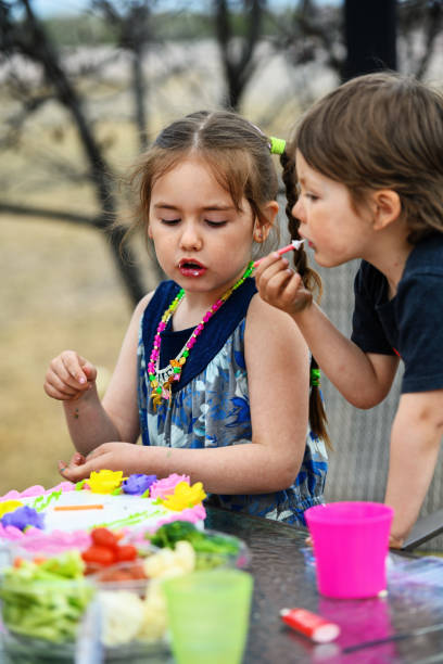Brother and sister licking birthday's candles stock photo