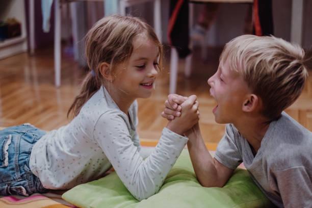 bruder und schwester lieben - armdrücken stock-fotos und bilder