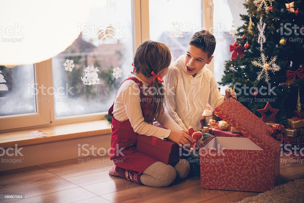 Brother and sister opening Christmas present stock photo