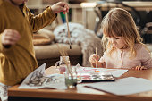 Close up of a brother and sister painting together.