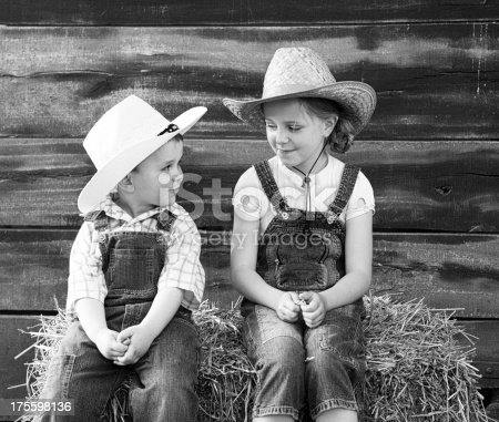 Brother and sister sitting on straw bales and wearing cowboy hat. Film grain added for the mood.