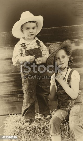 Brother and sister sitting on straw bales and wearing cowboy hat. Aged and film grain added for the mood.