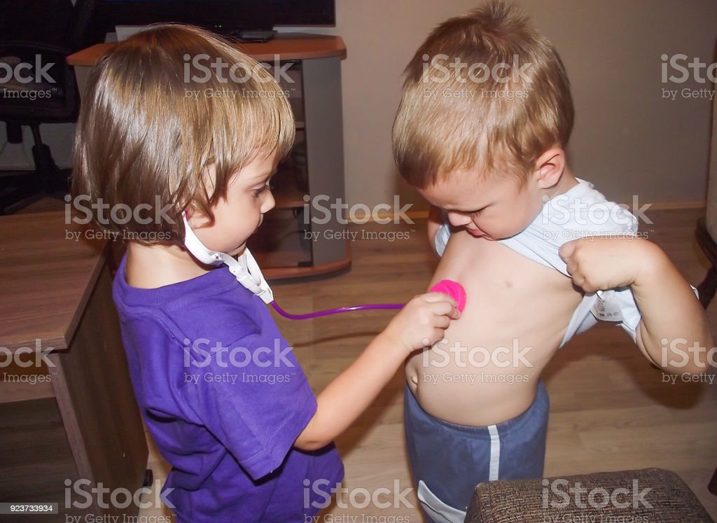 Brother and sister play doctor stock photo