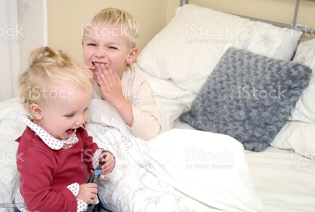 Hermano y hermana jugando en casa en la cama foto de stock libre de derechos