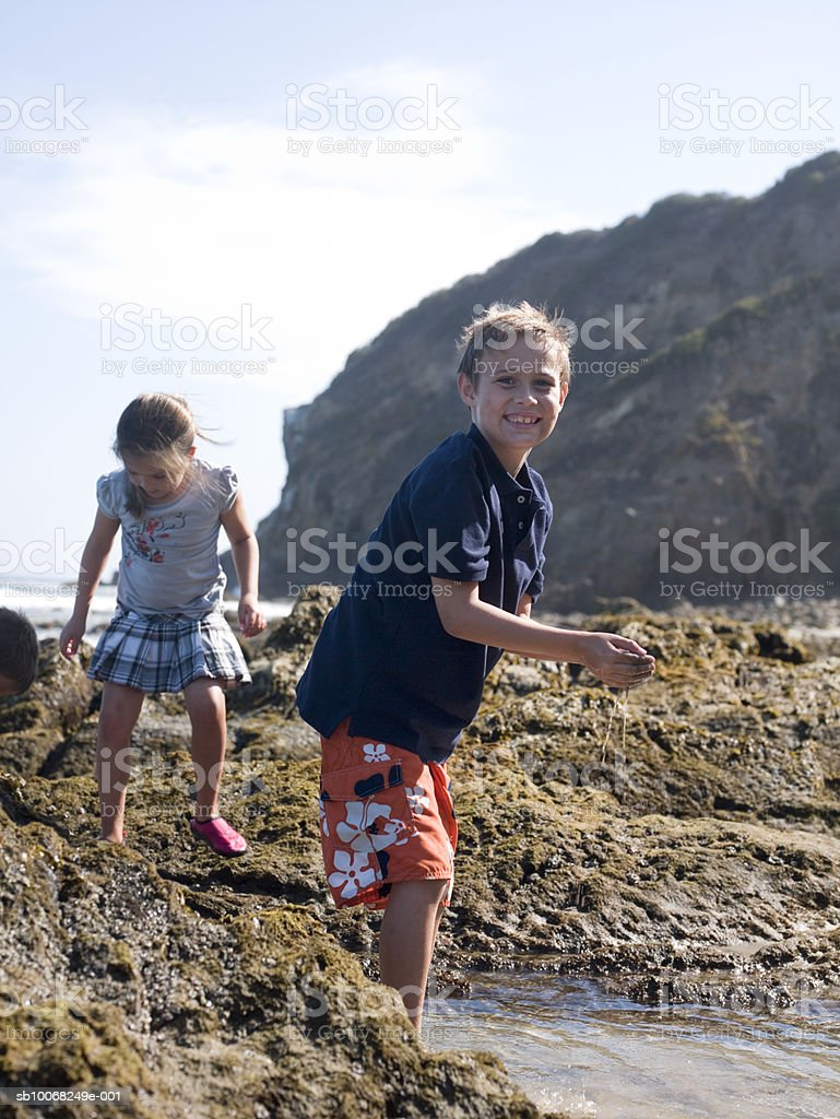 Brother and sister (6-9) playing at seashore, boy looking at camera royalty free stockfoto