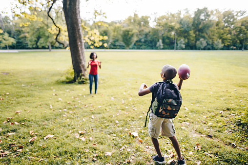 istock brother and sister playing football in the park 867047546
