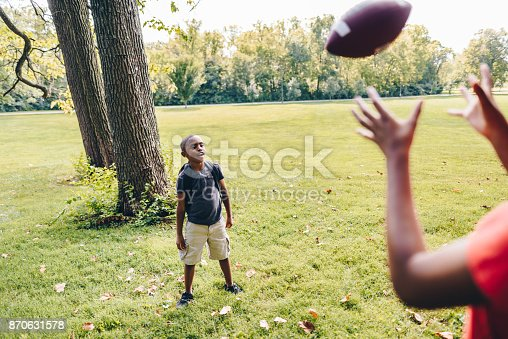 istock brother and sister playing football in the park 870631578