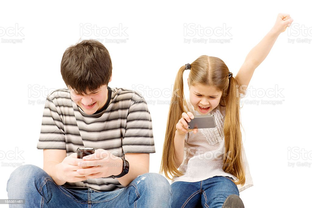Brother and Sister playing games on mobile phones royalty-free stock photo