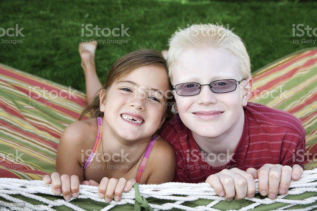 Brother and sister playing in a hammock stock photo