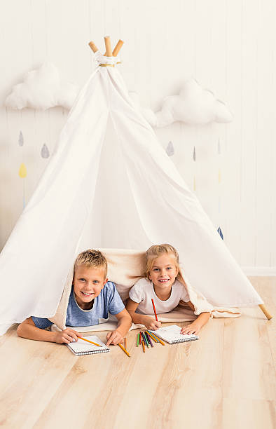 brother and sister playing in lodge - tipi zelt stock-fotos und bilder