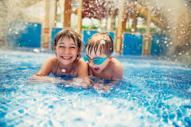 Brother and sister playing in resort pool. stock photo