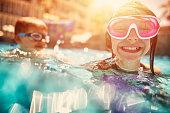 Kids swimming, laughing and having fun in hotel resort pool.\n\n