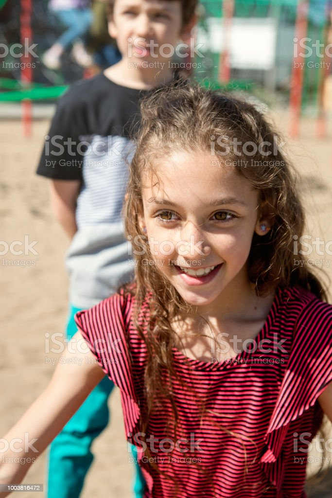 Brother and sister playing in school playground at recess.. stock photo