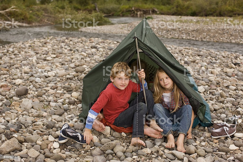 Brother and sister playing in small tent royalty free stockfoto