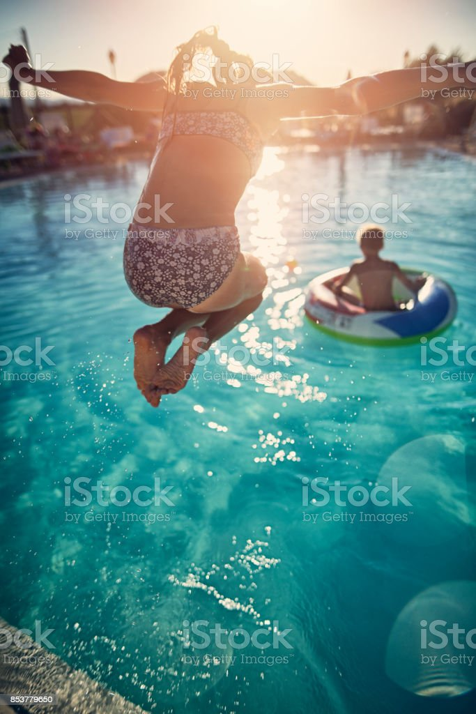 Brother and sister playing in the resort pool - foto stock