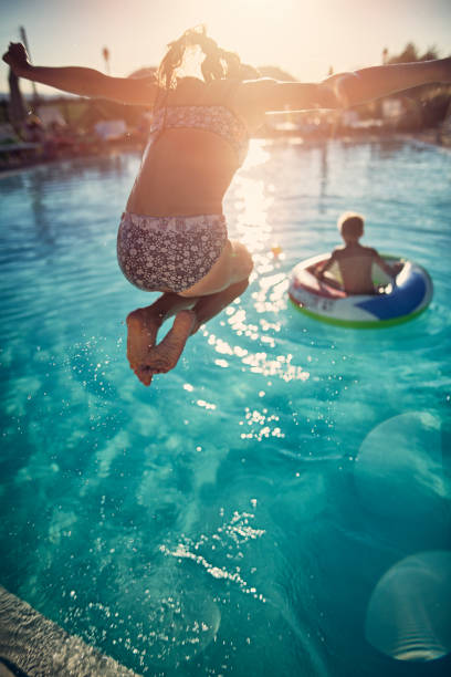 brother and sister playing in the resort pool - jumping into water stock pictures, royalty-free photos & images