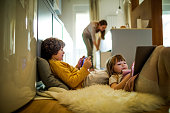 Close up of a brother and sister playing mobile games together while their mom is working in the kitchen