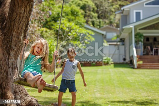 Brother and sister take turns swinging each other on their tree swing.