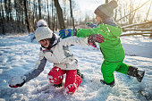 Brother and sister playing and laughing in winter forest. The kids are throwing snowballs and fighting. The snow is falling, trees are covered in snow.