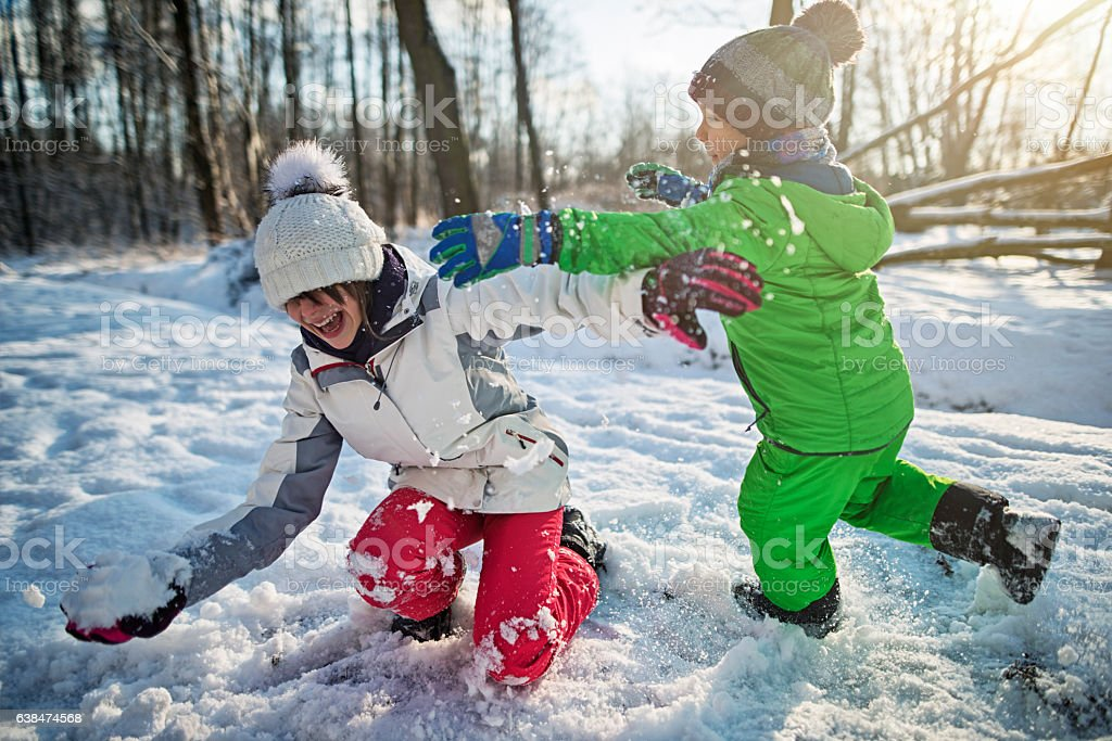 Brother and sister playing showball fight in winter forest - Photo