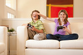 Brother and sister playing video games at home together