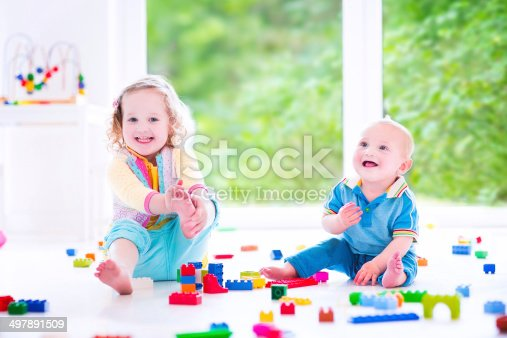 470874196istockphoto Brother and sister playing with colorful blocks 497891509