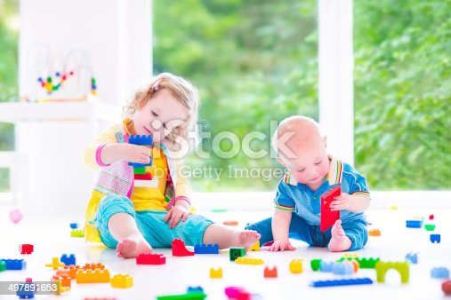470874196istockphoto Brother and sister playing with colorful blocks 497891653