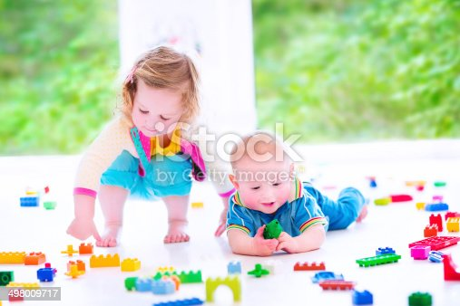470874196istockphoto Brother and sister playing with colorful blocks 498009717