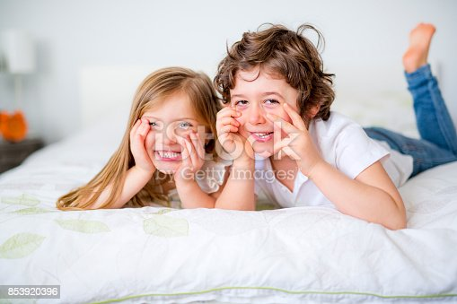 istock Brother And Sister Relaxing Together In Bed 853920396