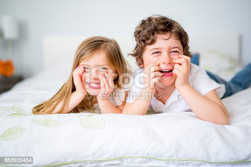 istock Brother And Sister Relaxing Together In Bed 853920454
